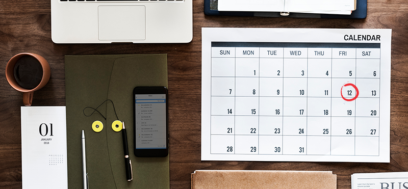 Wood filled office desk with monthly calendar with the date of the 12th circled in red